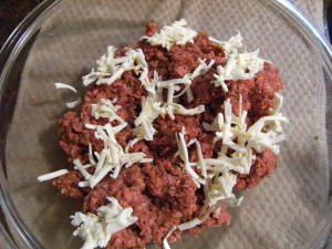 ground beef with shredded butter being mixed in.