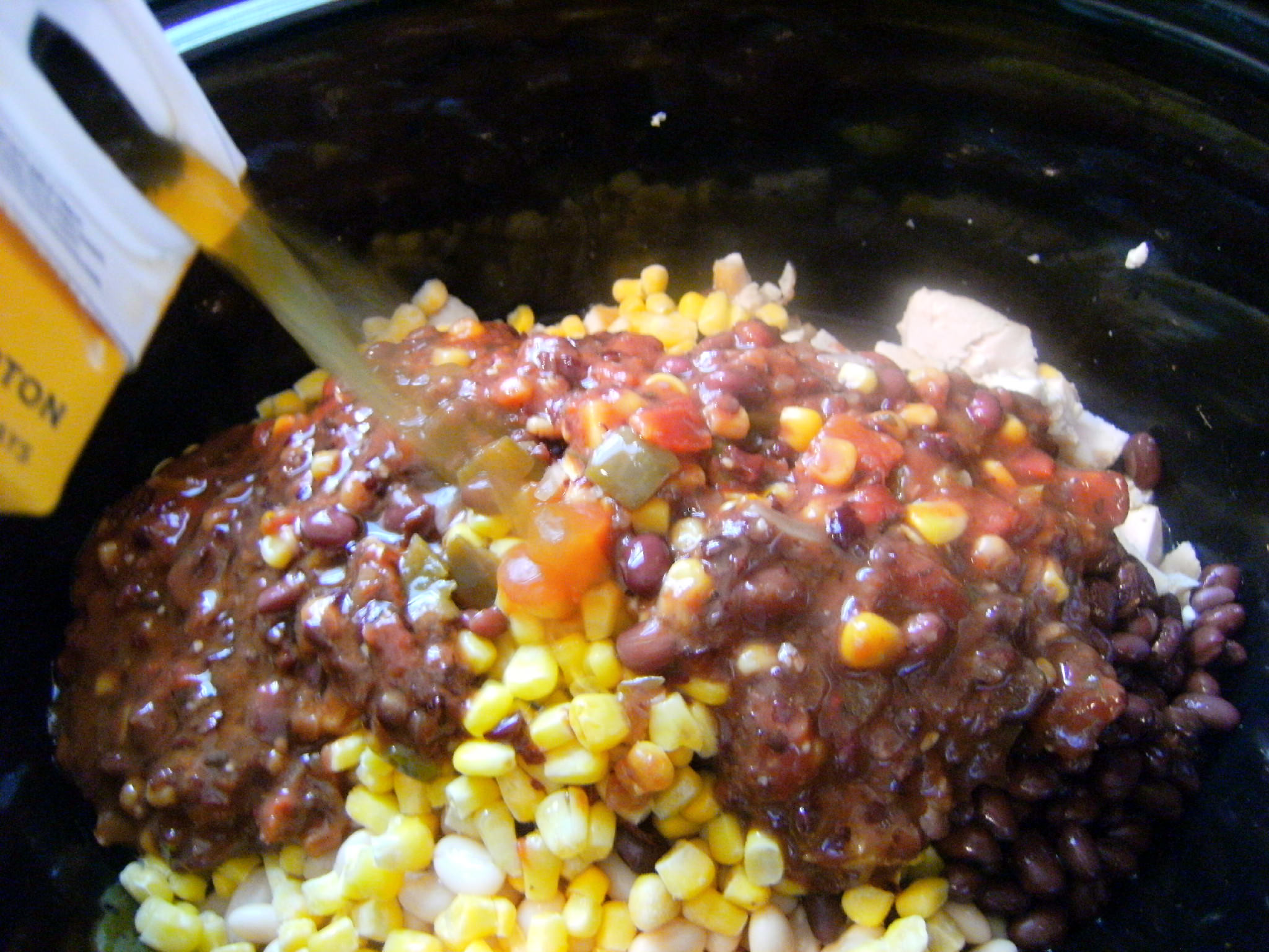 adding ingredients needed to make slow cooker chicken chili