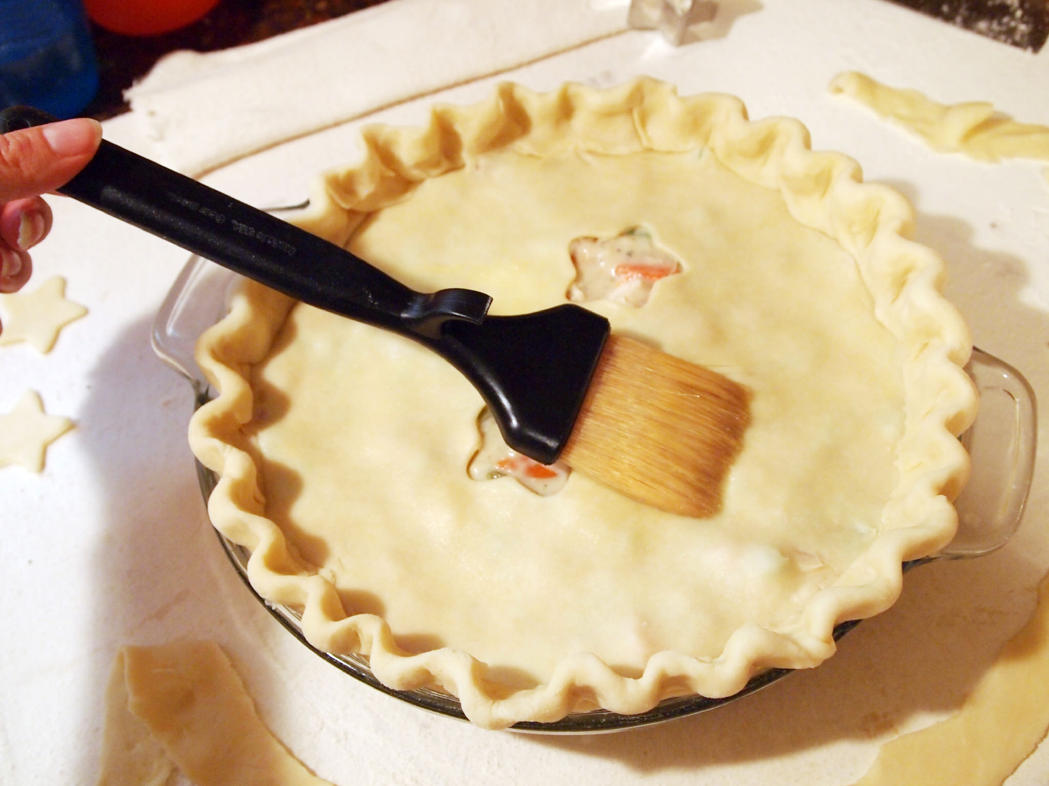 applying egg wash to the crust of a chicken pot pie