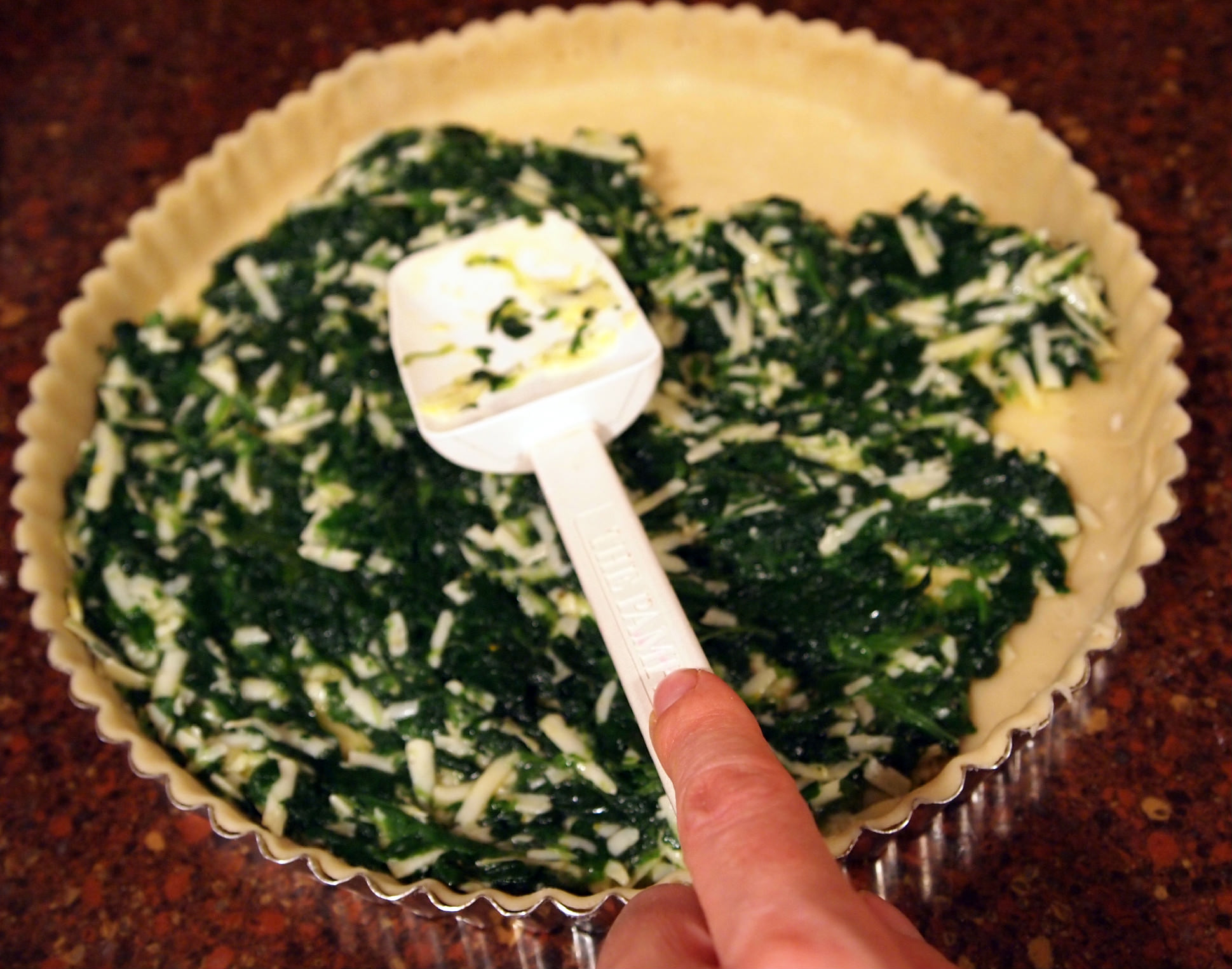 spreading filling into a spinach tart