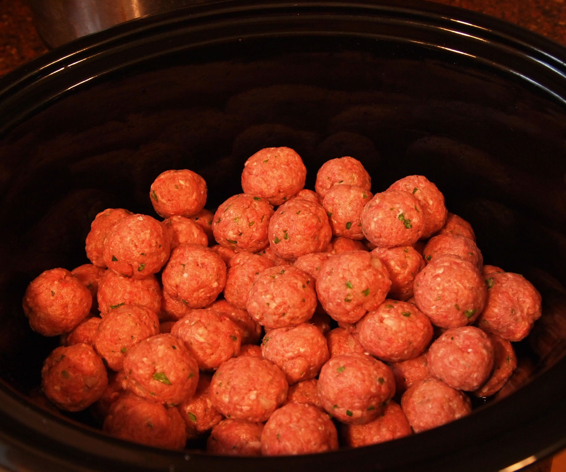 Game-Day-Meatballs are simmered all day in a crock pot until super tender and bathed in a flavorful sweet & spicy sauce made with grape jelly.
