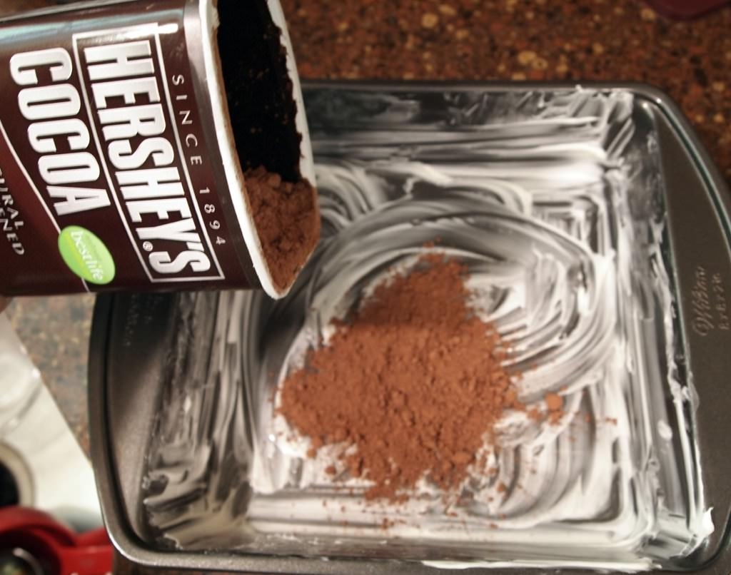 greasing a cake pan and dusting it with cocoa powder
