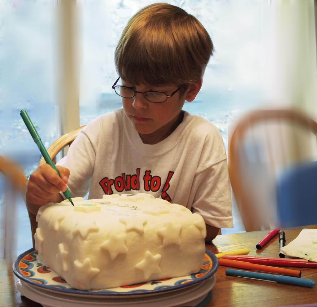 Young boy decorating a cake with fondant