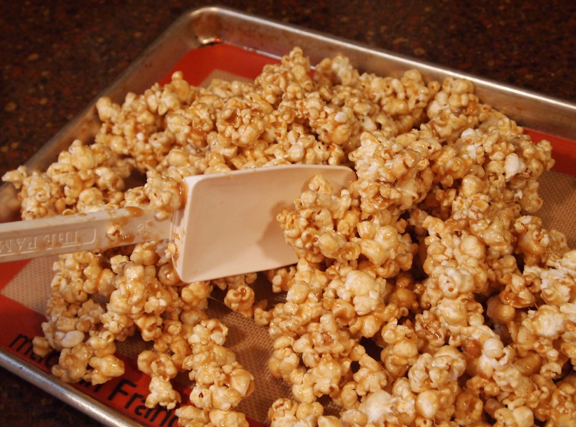 divide vanilla caramel corn between baking sheets