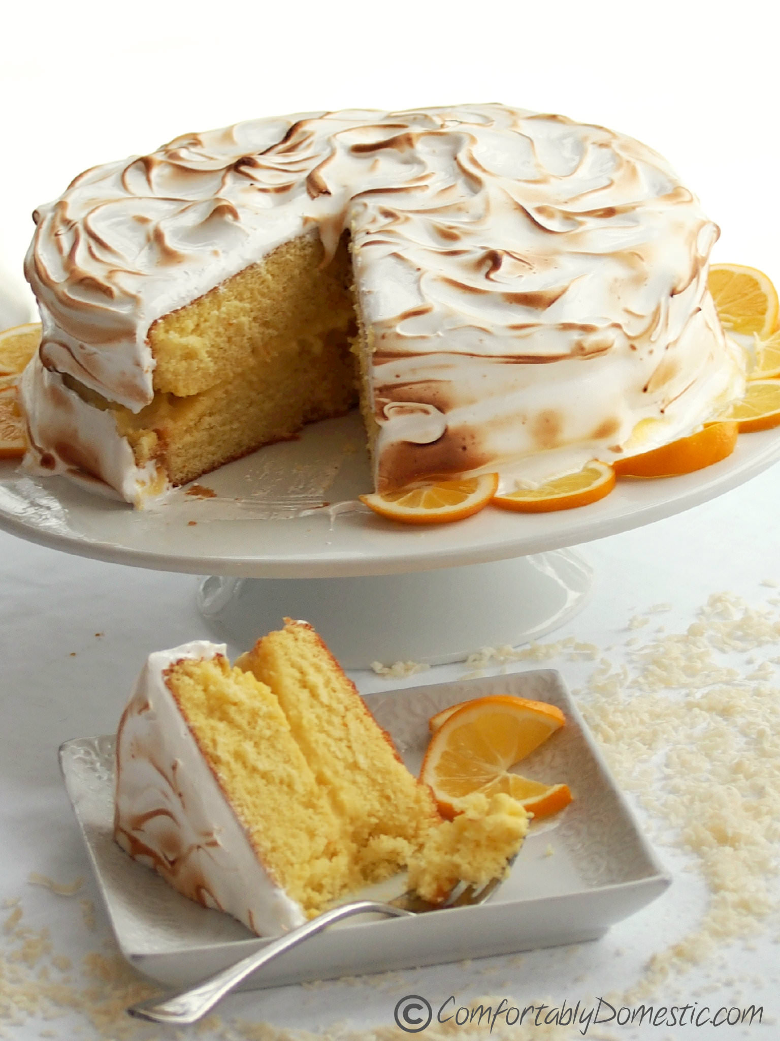 Coconut Meyer Lemon Meringue Cake - The balance of flavors and textures between moist cake, creamy lemon curd, and toasted Swiss meringue makes this Coconut Meyer Lemon Cake recipe a winner! | ComfortablyDomestic.com