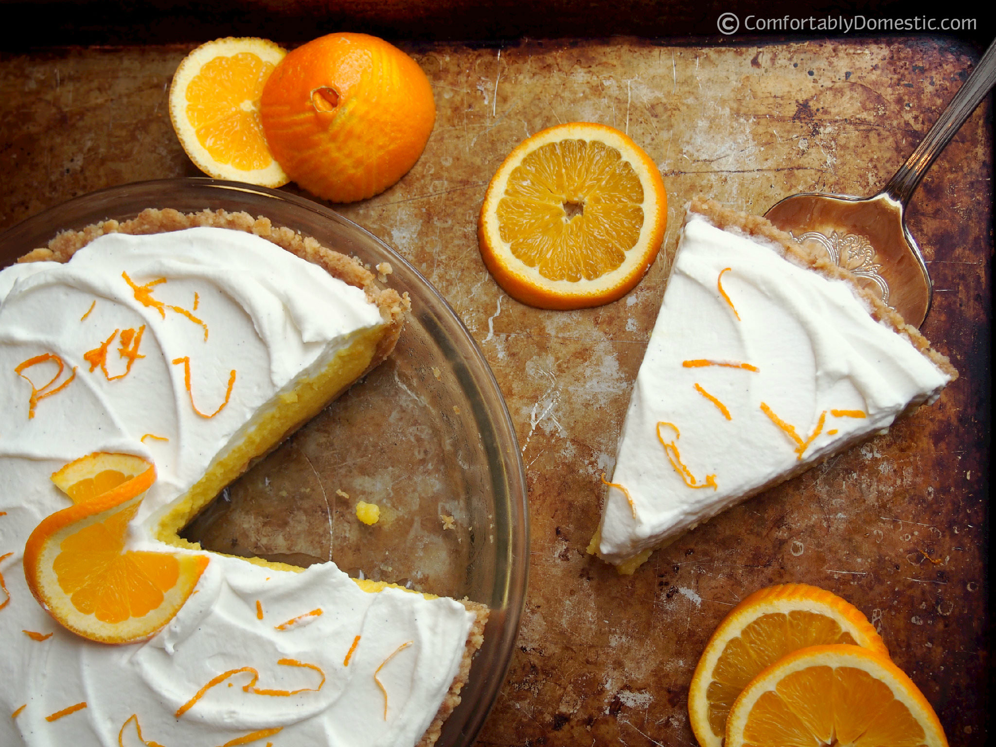 Orange cream pie is sweet-tart orange curd nestled on a Nilla wafer cookie crust, then topped with lightly sweetened whipped cream. | ComfortablyDomestic.com
