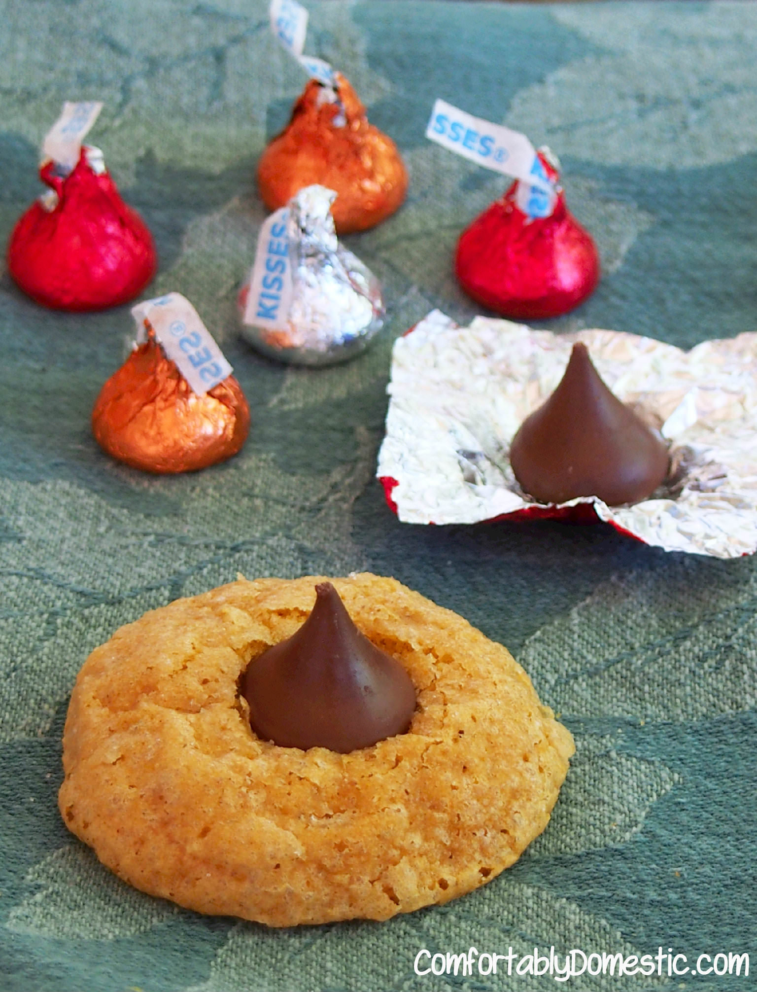 Pumpkin kiss cookies are the classic holiday favorite, with a kick! Deliciously soft and spicy pumpkin cookies with a fat kiss of chocolate in the center.