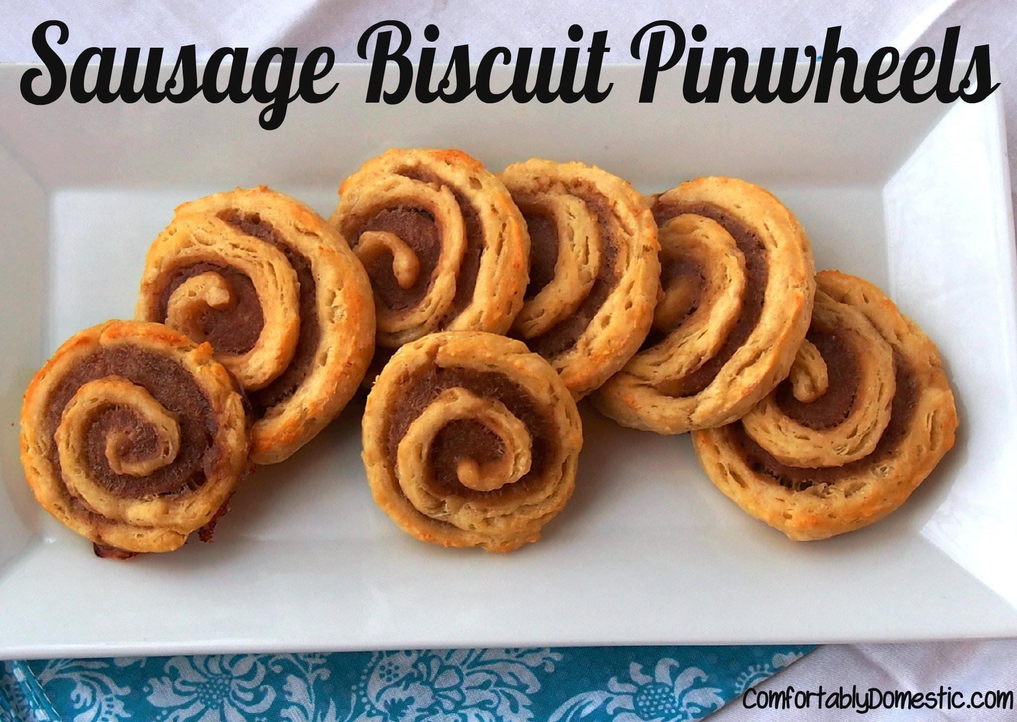 Sausage biscuit pinwheels are an easy appetizer to make. Tangy, buttery biscuit dough wraps around savory sausage for deliciously and attractive appetizer. | ComfortablyDomestic.com