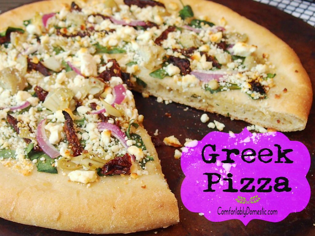 Greek Pizza starts with a tangy tzatziki sauce that unites such Mediterranean flavors as artichoke hearts, sundried tomatoes, spinach, red onion, and a feta cheese into tantalizing, cornmeal-crusted pizza. | ComfortablyDomestic.com