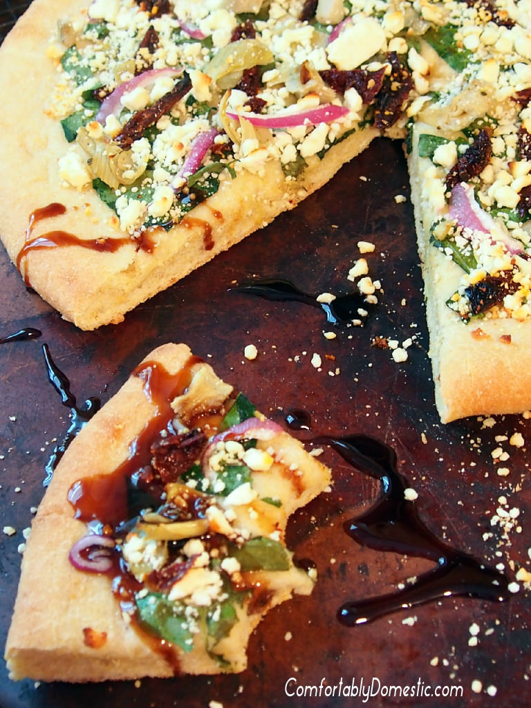 Greek Pizza-with-Balsamic-Glaze starts with a tangy tzatziki sauce that unites such Mediterranean flavors as artichoke hearts, sundried tomatoes, spinach, red onion, and a feta cheese into tantalizing, cornmeal-crusted pizza. | ComfortablyDomestic.com
