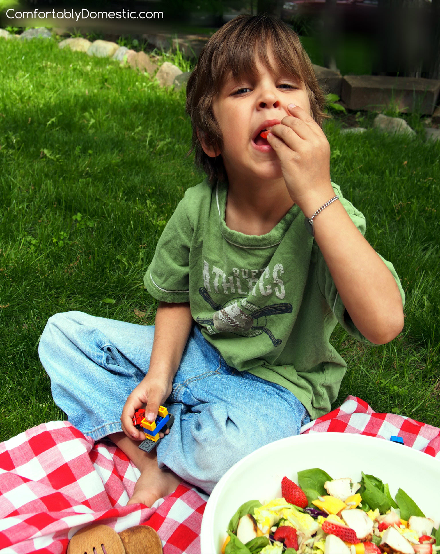 The Baby plucking strawberries out of the salad.