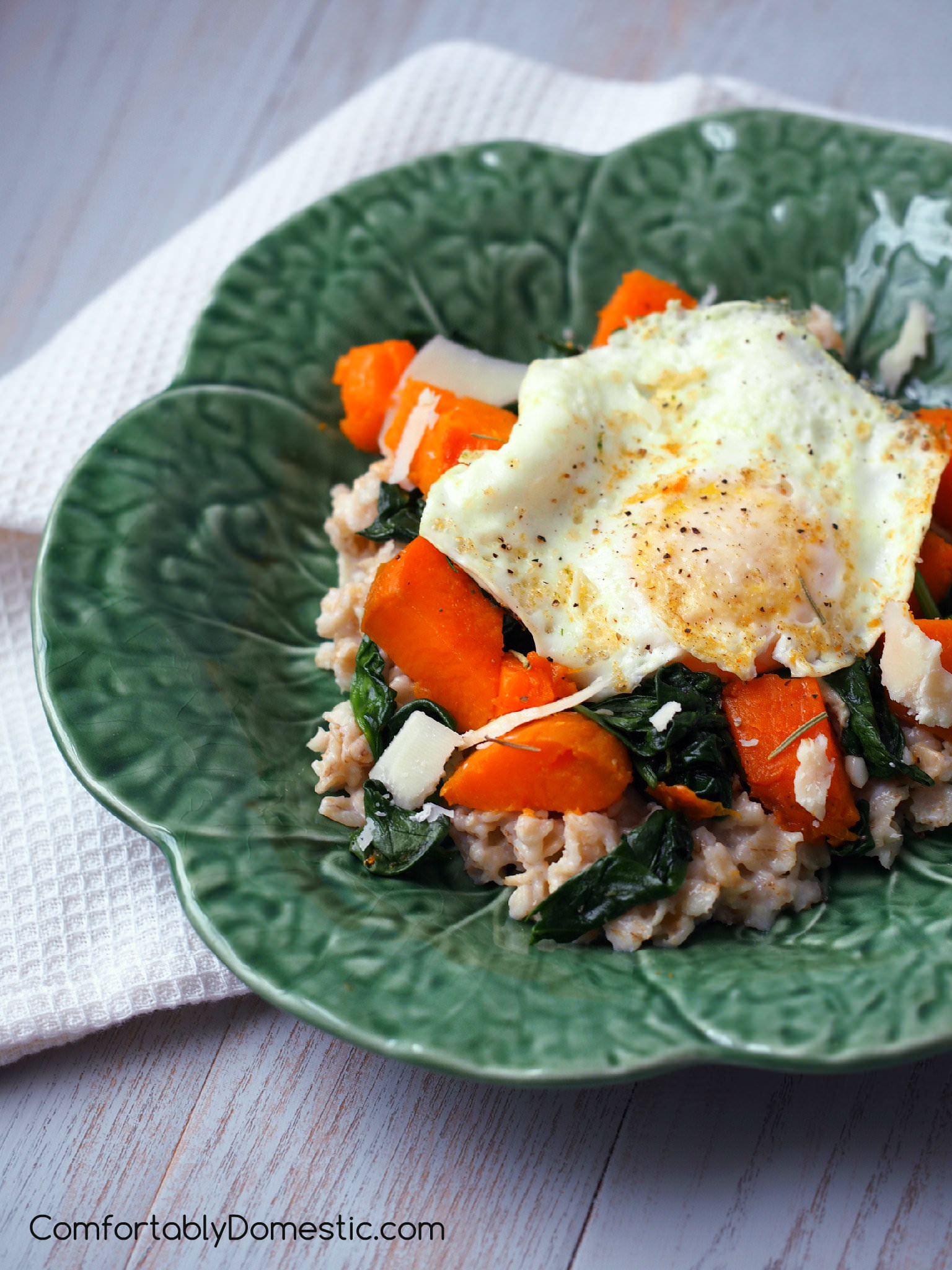 Savory oats are an infinitely satisfying way to start the day! Vibrant spinach, roasted sweet potatoes, and a farm fresh egg rest atop a bed of healthy oats for a delicious breakfast. | ComfortablyDomestic.com