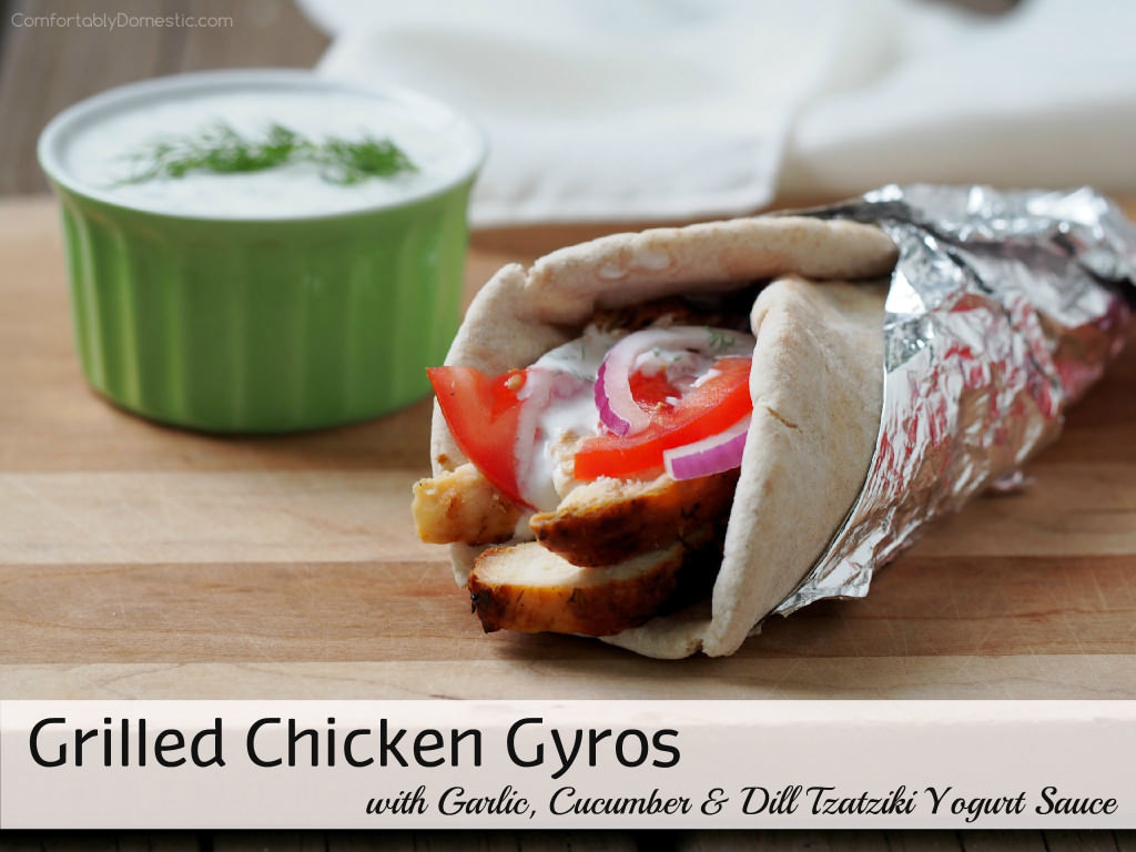 Grilled-Chicken-Gyros - Tender, souvlaki-style grilled chicken topped with a flavorful garlic, dill, and cucumber tzatziki yogurt sauce, ripe tomatoes, and thinly shaved red onion wrapped in warm pita bread. | ComfortablyDomestic.com