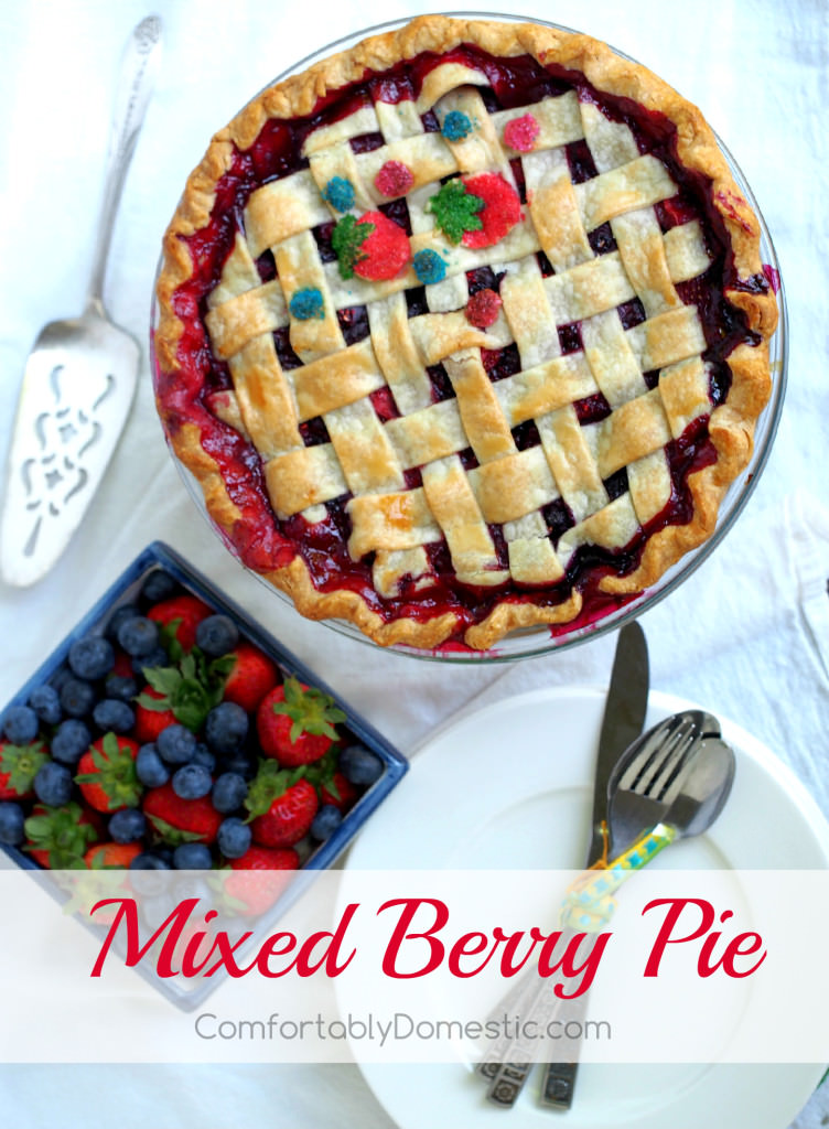 Mixed berry pie that is as delightfully inviting as summer itself. Fresh, sweet strawberries, juicy blueberries, and tart raspberries happily mingle together in a flaky pastry crust.  | ComfortablyDomestic.com