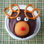 These adorable holiday cupcakes are decorated to look like reindeer! Pretzels for ears and cookies for the face. This cupcake recipe is lots of fun to make and easy, too! | ComfortablyDomestic.com