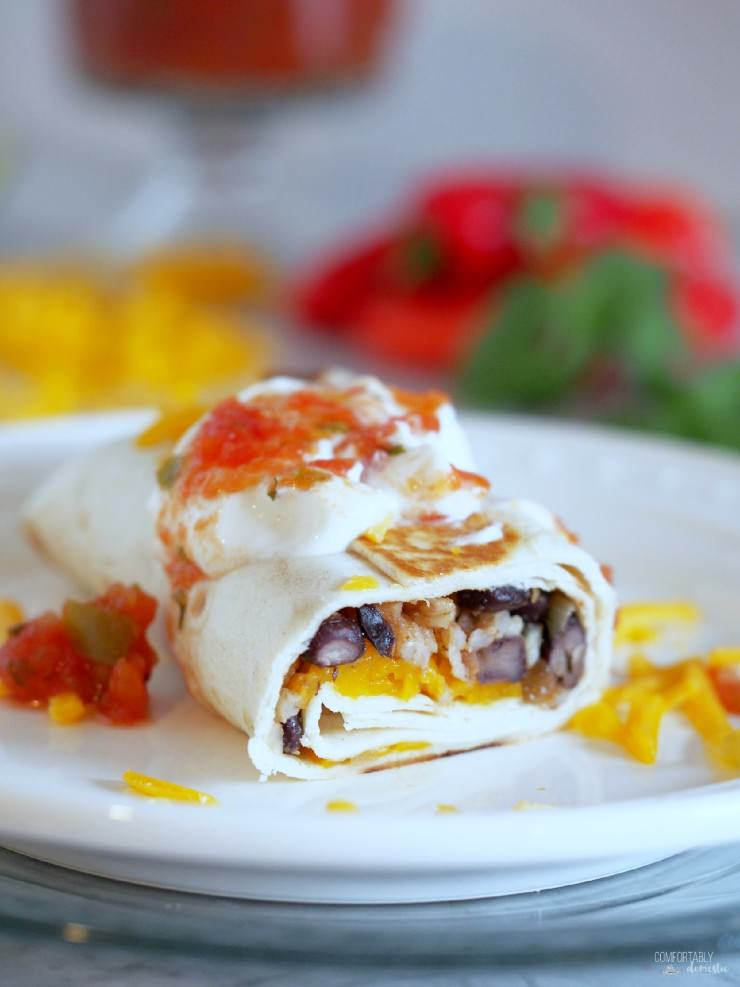Crispy-Black-Bean-Burritos combine black beans with sautéed vegetables, brown rice, and cheddar cheese for a healthy, balanced vegetarian meal with complete proteins, all wrapped in a toasted tortilla.